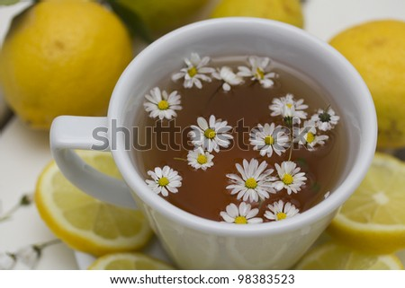 herbal tea with chamomile and lemon on a wooden table - stock photo