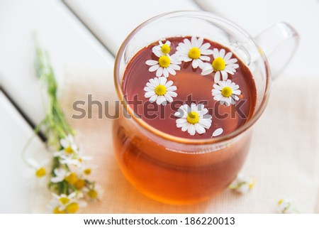 herbal tea with chamomile on a wooden table - stock photo