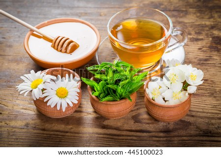 Herbal tea with mint, chamomile, jasmine flowers and honey on old wooden table - stock photo