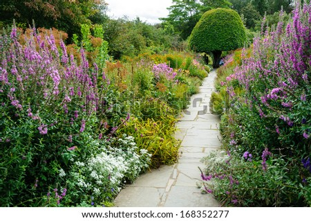 Herbatious Garden with stone patyway. - stock photo