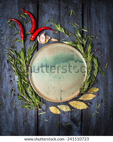 Herbs and spices around platte on dark blue wooden background, top view, place for text - stock photo