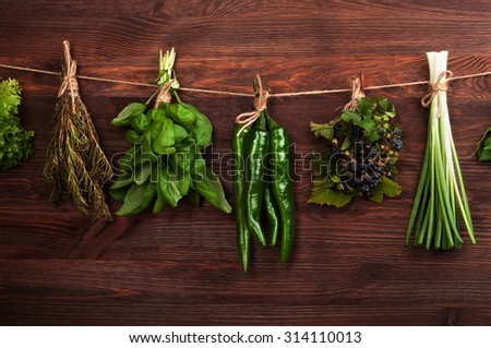 Herbs and spices; healthy eating; organic food; basil; hot peppers; papperoni;  green onion; rosemary; wooden board dark; ingredients for cooking; Cover for a cookbook;organic food; harvest - stock photo