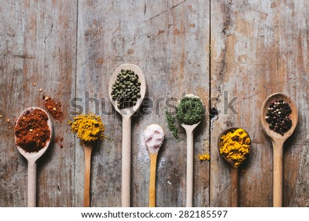 Herbs and spices in different shaped wooden spoons, top view, copy space, wooden table - stock photo