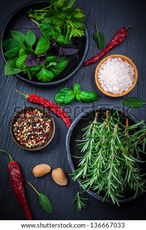 Herbs and spices on black background - stock photo