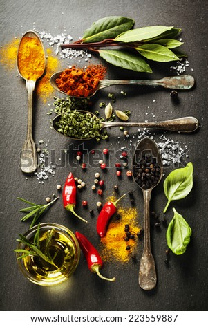 Herbs and spices selection - herbs and spices, old metal spoons and slate background - cooking, healthy eating - stock photo