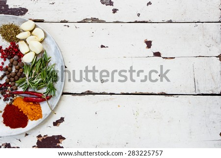 Herbs and spices selection on old metal platte over rustic wooden background, top view, place for text - stock photo