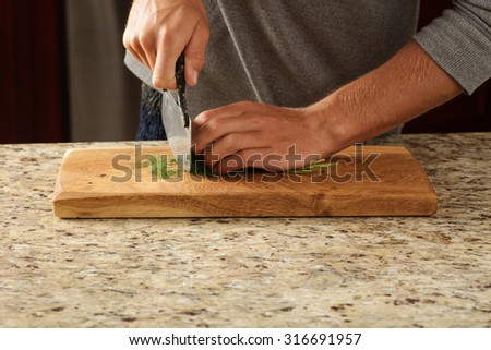 Herbs being chopped on a unique cutting board - stock photo