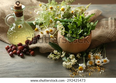 Herbs, berries and flowers with mortar, on wooden table background - stock photo