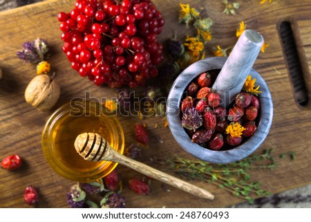 Herbs, berries in the marble pot on the brown wooden board, top view - stock photo