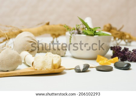 herbs, spices and massage pouches on white wooden table - stock photo