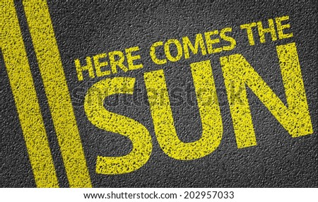 Here Comes the Sun written on the road - stock photo