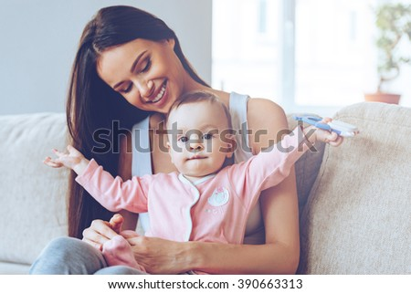 Here I am! Beautiful young woman holding baby girl with toy on her knee sand looking at her with love while sitting on the couch at home - stock photo
