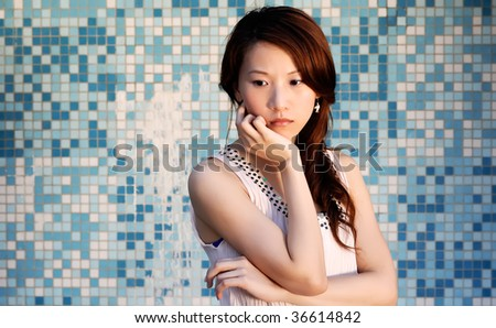 Here is a beautiful Asian lady in front of mosaic and think. - stock photo