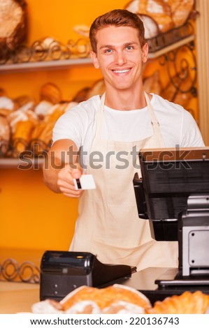 Here is your card! Handsome male cashier stretching out plastic card and smiling while standing in bakery shop  - stock photo