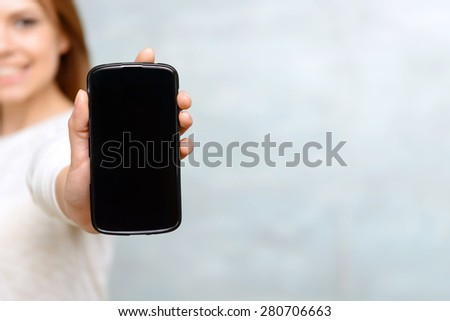Here it is. Close up of mobile phone showed by young smiling woman on isolated background. - stock photo