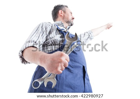Hero shot with young mechanic pointing finger up and holding spaneer isolated on white background - stock photo