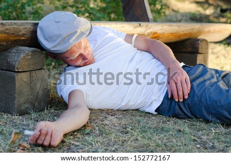 Heroin abuser fallen down with his left arm tied with a belt and a syringe in his right hand - stock photo