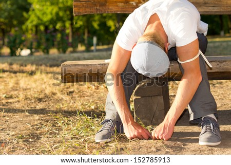 Heroin abuser sitting on a bench in the park while experiencing nausea after taking an injectable drug dose - stock photo