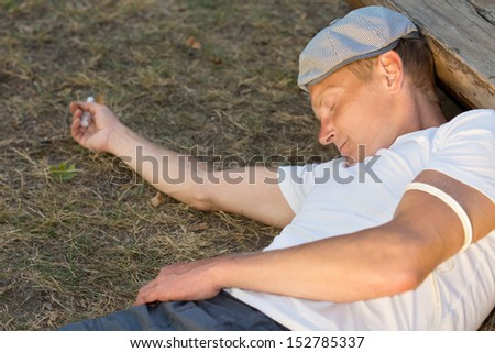 Heroin user experiencing unconsciousness after drug dose administered intravenously - stock photo