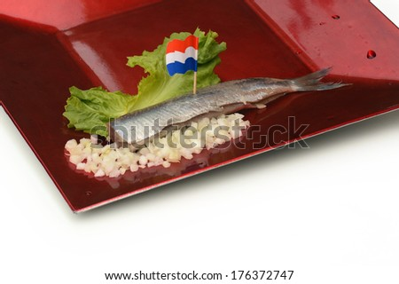 Herring fillet with Dutch flag, chopped onions and lettuce on a red plate - stock photo