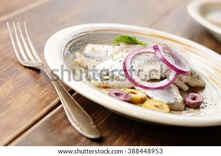Herring fillets served with olives onions and dill on wooden table - stock photo