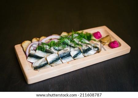 herring with potatoes chips, horseradish and mustard - stock photo