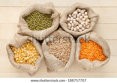 hessian bags with cereal grains: red lentils, peas, chick peas, wheat and green mung on wooden table, top view - stock photo