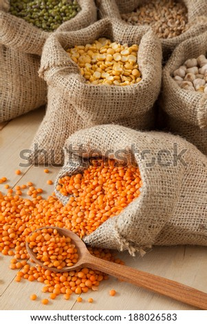 hessian bags with red lentils, peas, chick peas, wheat and green mung on table - stock photo
