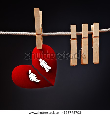 Heterosexual couple breaking apart, conceptual love image of paper heart ripped in two, hanging on rope with clothes pin. - stock photo