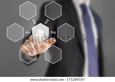 Hexagonal button pressed by businessman on grey background - stock photo