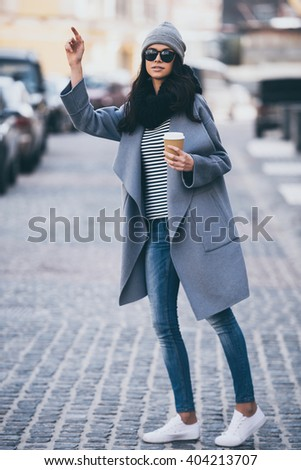 Hey taxi! Full length of beautiful young woman in sunglasses holding coffee cup and waving for taxi while standing outdoors - stock photo