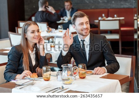 Hey there. Business managers in official attire wave with a friendly smile to the familiar people while having business lunch at the restaurant - stock photo