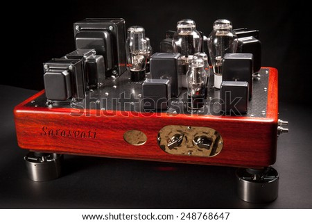 Hi fi amplifier with electronic vacuum tubes devices. Wood chassis and carbon fiber plates. Studio photos and dark background - stock photo