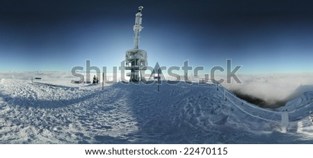 hi-resolution panorama on a winter evening on mt. rigi in central switzerland. sun hidden behind icy telecoms and tv tower. fog covering lower landscape - stock photo