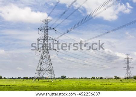 Hi-voltage electrical pylons against blue sky - stock photo