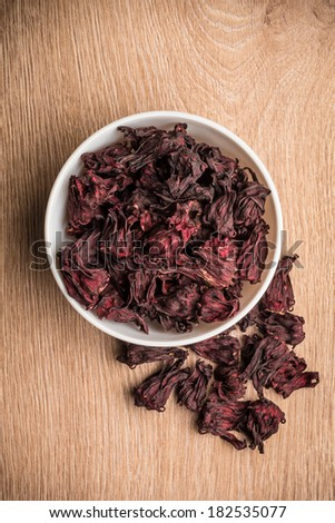 Hibiscus Leaves in a white bowl on a wooden surface - stock photo