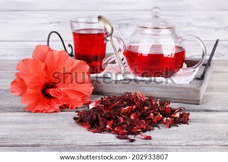 Hibiscus tea in glass teapot and flower on color napkin on wooden background - stock photo