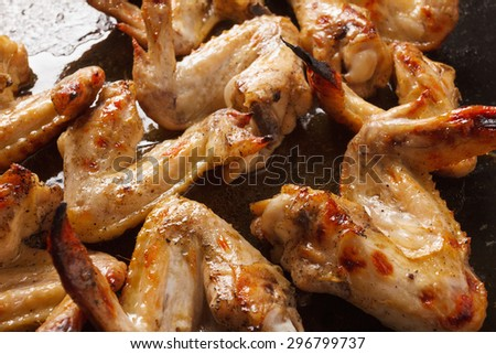 hicken wings with pepper in a frying pan in the kitchen cooking a delicious dinner. Ready meal with crispy crust - stock photo