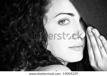 Hidden woman staring at camera, black and white toned. - stock photo