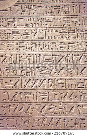 Hieroglyphic text carved into sandstone - stock photo