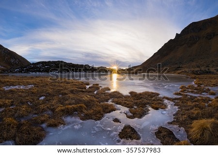 High altitude alpine lake in idyllic land. Reflection of the sunlight on the frozen surface. Glowing sunstar at the horizon at sunset. Ultra wide angle shot taken on the Italian Alps at 2500 m asl. - stock photo