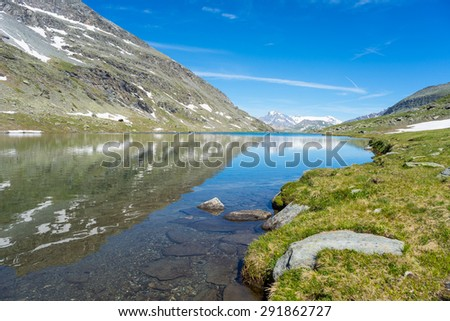High altitude blue lake in idyllic uncontaminated environment once covered by glaciers. Summer season in the Italian French Alps. Wide angle view, snowcapped mountains reflected on water surface. - stock photo