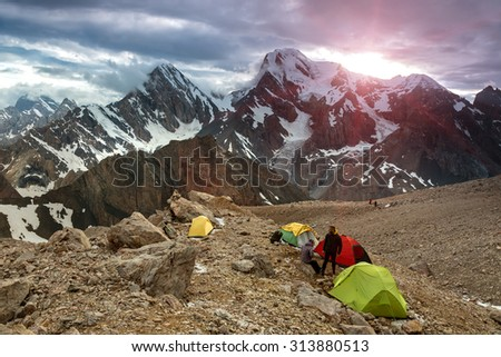 High Altitude Camp Changing Weather Sunbeams above Cloud Level at Mountain Peaks of Fan Valley in Tajikistan Tents of Extreme Climbers Bivouac on Rocky Moraine - stock photo