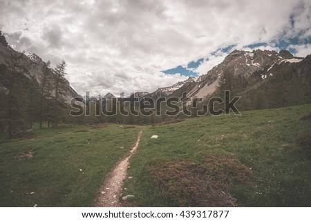 High altitude extreme terrain, rocky mountain peak and jagged ridge, with scenic dramatic stormy sky. Wide angle view in backlight. Toned image. - stock photo