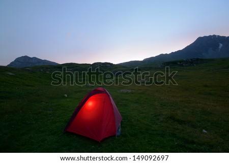 High altitude idyllic alpine landscape at dusk, with glowing tent. Location: Col du Petit Mont Cenis, Savoie, France. - stock photo