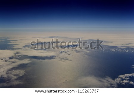 High altitude view of the atmosphere. Clouds over the ocean. - stock photo