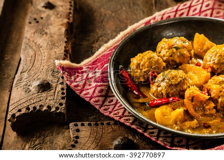 High Angle Close Up of Traditional Tajine Berber Dish of Meatballs Smothered in Spicy Yellow Curry Sauce with Hot Red Peppers and Served in Shallow Bowl on Cloth Napkin and Rustic Wooden Table - stock photo