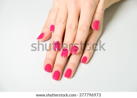 High Angle Close Up of Woman Applying Bright Pink Colored Nail Polish to Finger Nails Using Brush with Bottle Close By on White Surface with Copy Space - stock photo