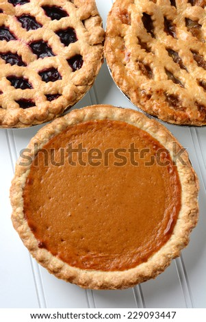 High angle closeup of three fresh baked holiday pies. The traditional American desserts - Pumpkin, Cherry and Apple pie are Thanksgiving staples. Vertical format. - stock photo