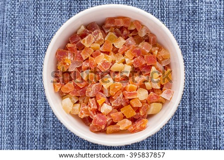 High angle directly above white bowl filled with diced cubes of dehydrated Carica papaya on blue fabric placemat - stock photo